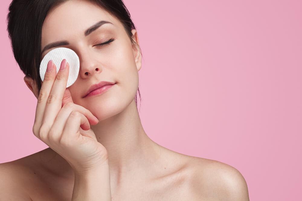 Mulher passando almofada de maquiagem na região dos olhos