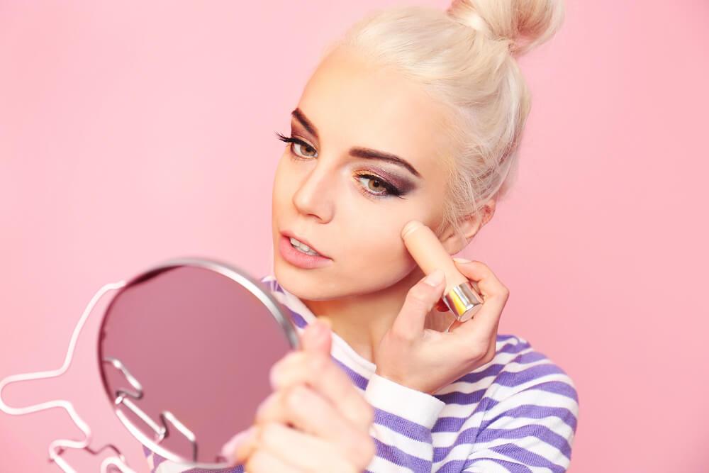 Mulher passando almofada de maquiagem na região dos olhos e bochechas