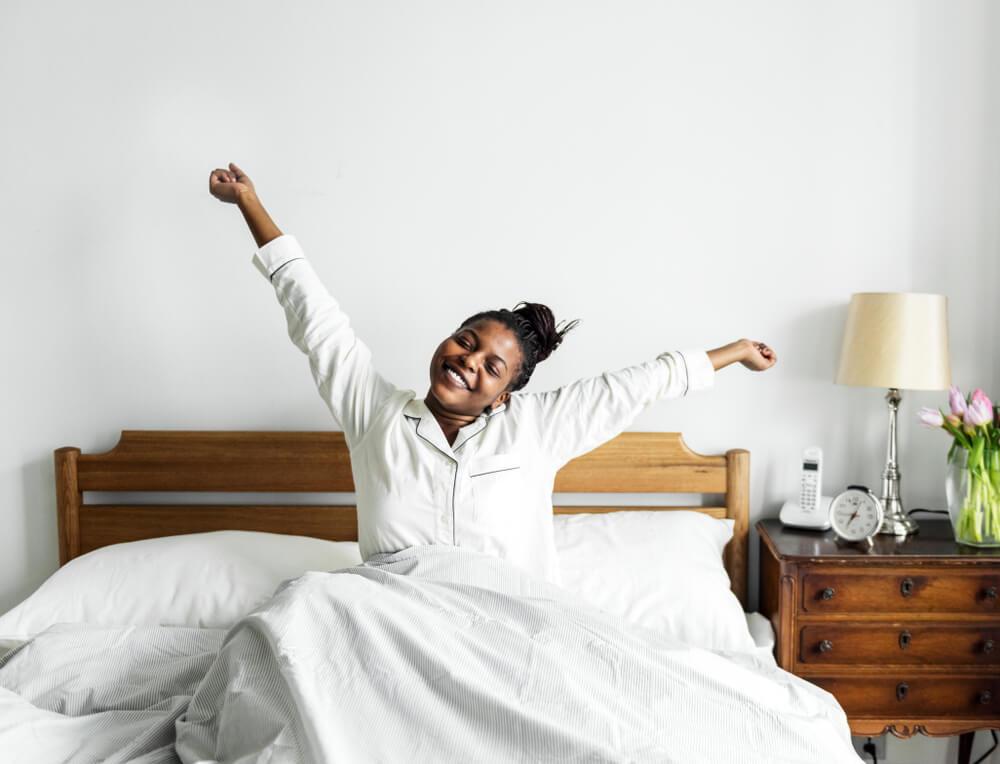 Mulher acordando e se espreguiçando na cama