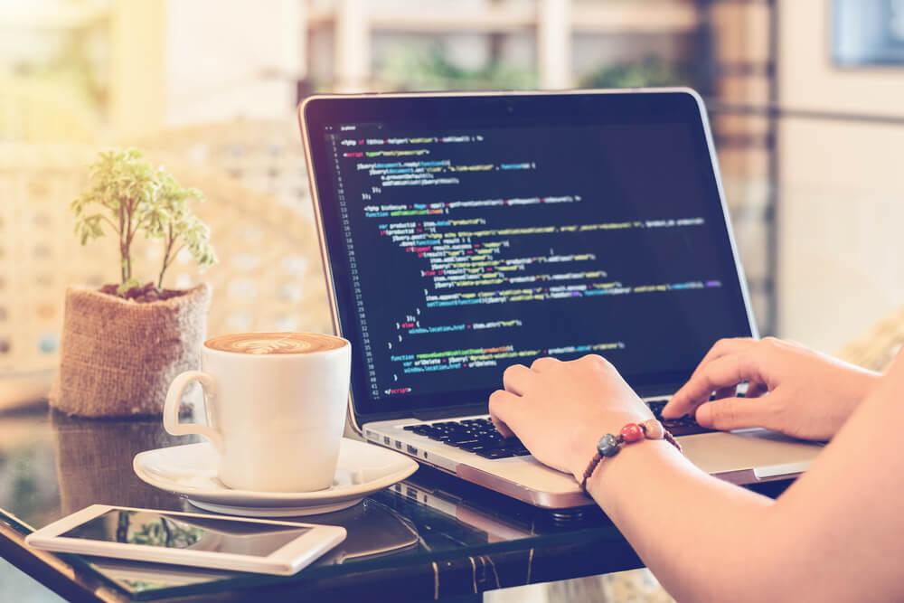 Menina em frente ao computador com software de programação aberto e um copo de café ao seu lado