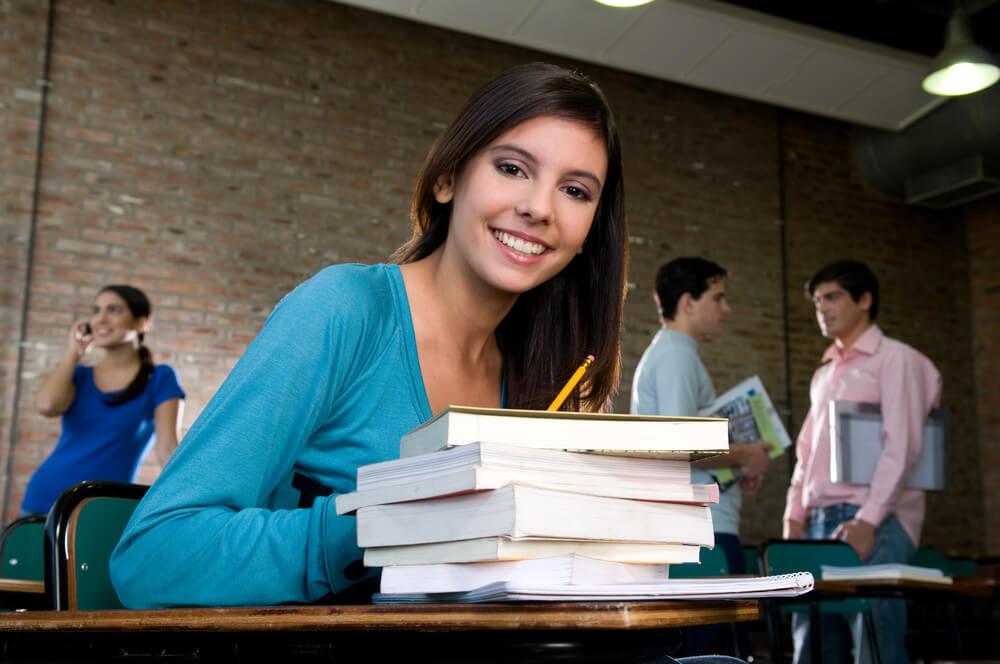 Menina sentada com uma pilha de livros em mesa à sua frente
