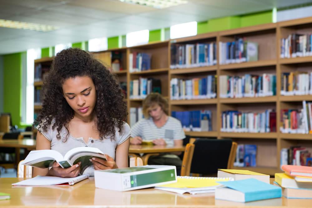 Menina lendo livro sentada à mesa em uma biblioteca