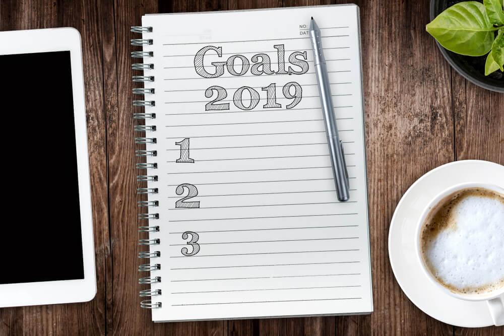 Caderno apoiado em mesa com lista de objetivos para 2019