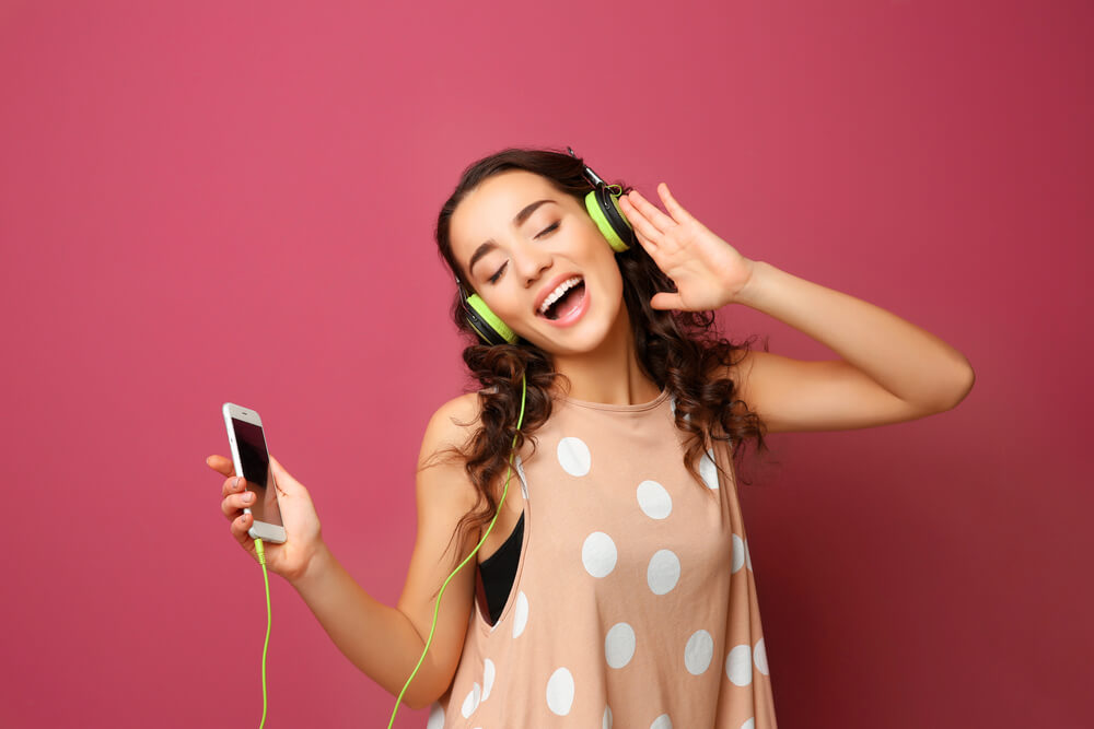 Menina escutando músicas em fones de ouvido conectados ao celular