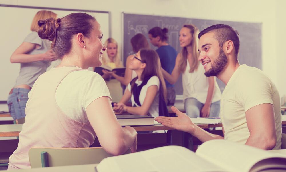 Estudantes conversando em sala de aula lotada