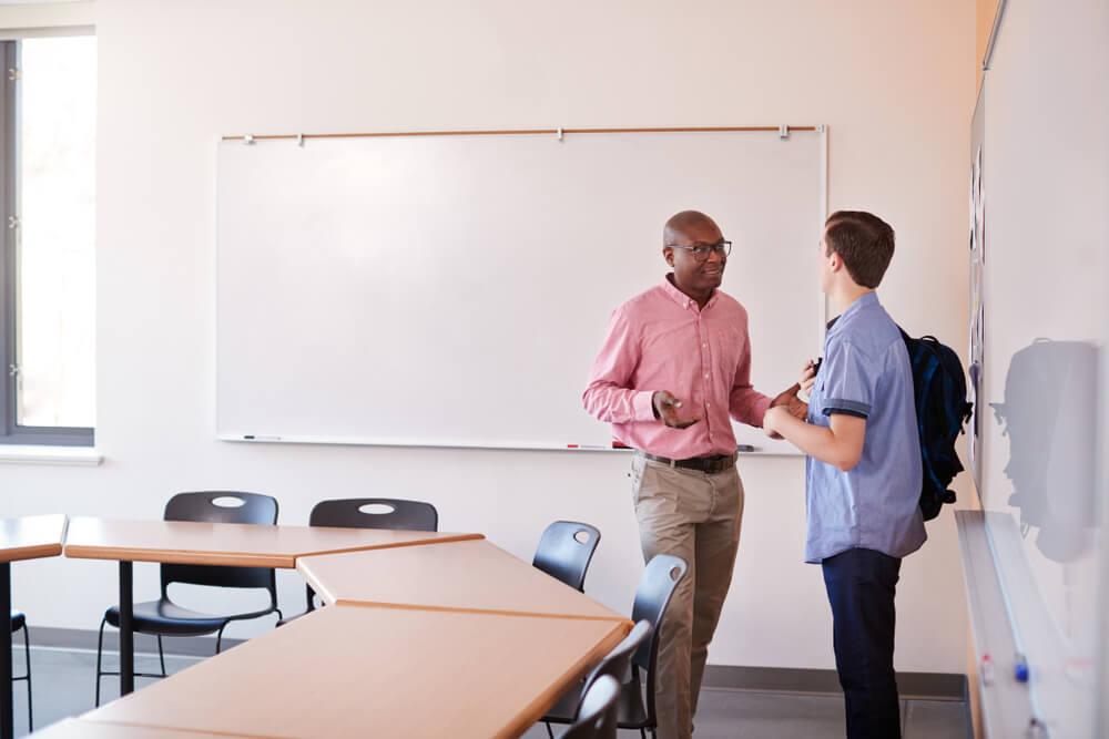 Professor conversando com aluno em frente ao quadro negro