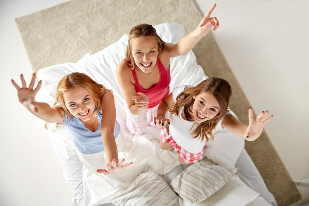 Três meninas de pé em uma cama