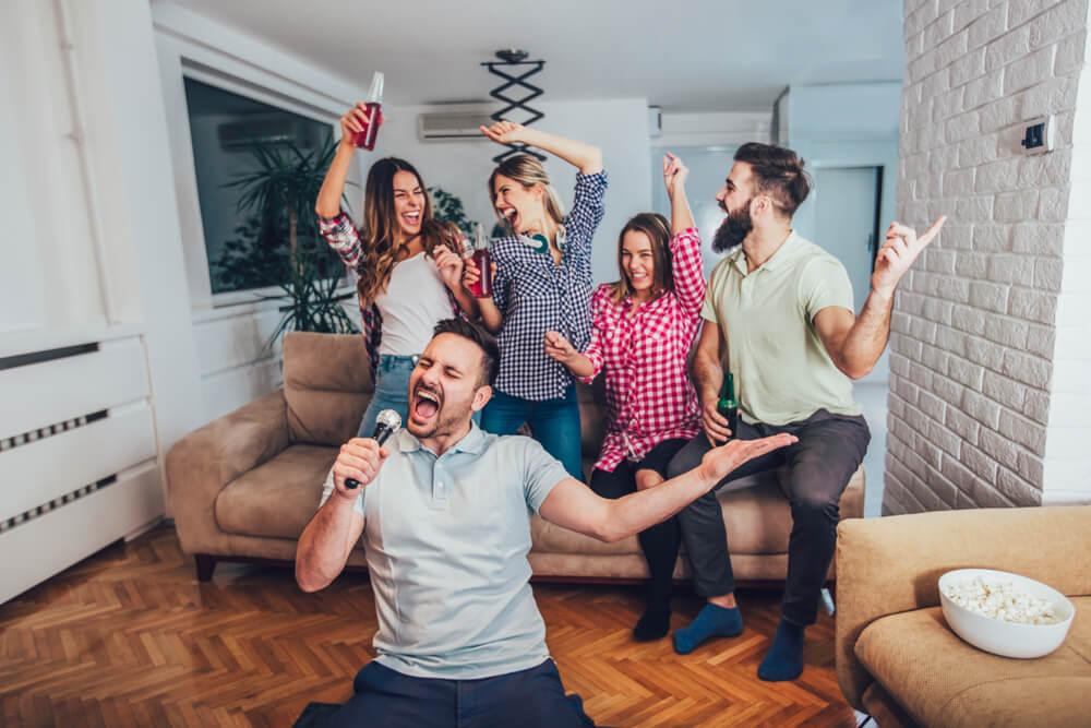 Amigos cantando e dançando em frente ao karaoke