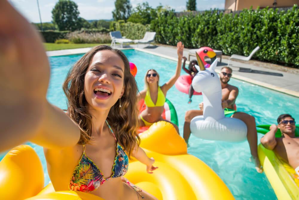 Amigos sentados em boia dentro de uma piscina